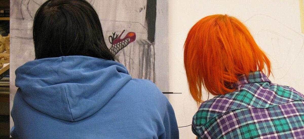 Kaksi henkilöä selin jotka katselevat seinällä olevaa maalausta.