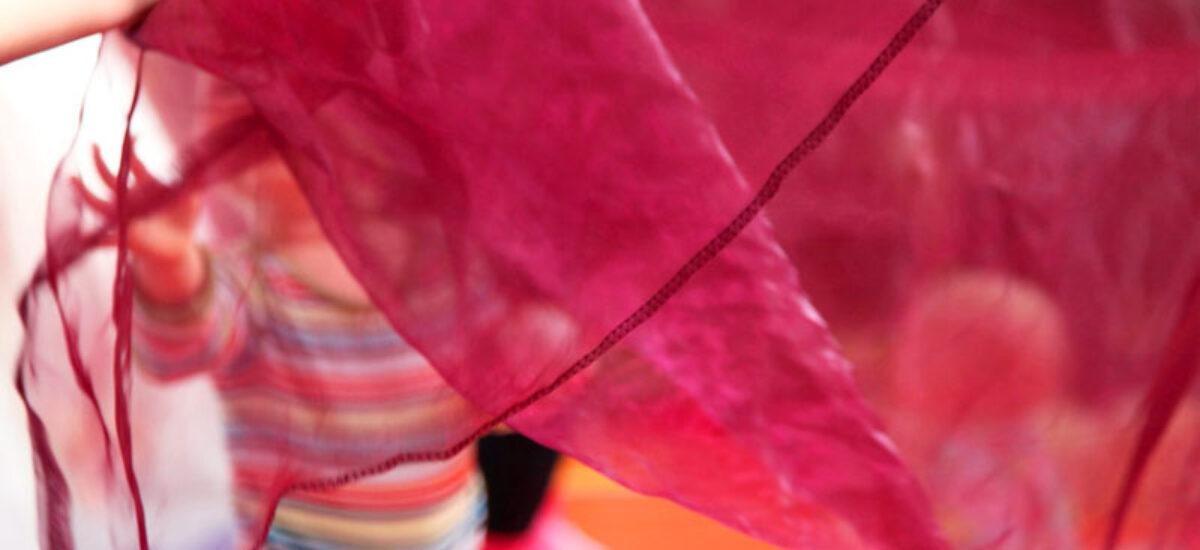 Aniliininpunainen läpikuultava huivi jonka takana seisoo pieni lapsi. Lapsen päällä raidallinen pusero.