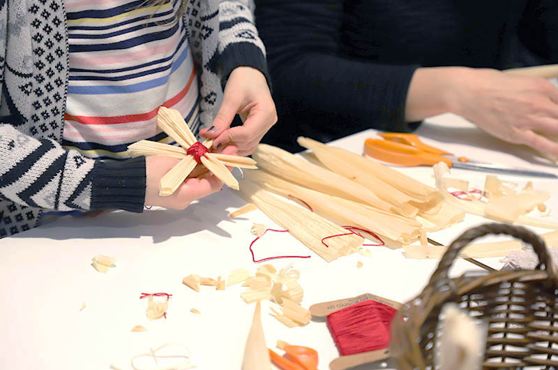 Lapsen ja aikuisen kädet. Lapsella on käsissään tähden muotoinen koriste, jota hän parhaillaan valmistaa. Pöydällä on sakset ja erilaisia rakentelumateriaaleja.
